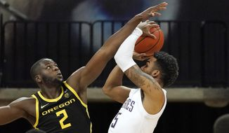 Oregon's Eugene Omoruyi (2) defends against a shot by Washington's Jamal Bey during the second half of an NCAA college basketball game Saturday, Dec. 12, 2020, in Seattle. (AP Photo/Elaine Thompson)