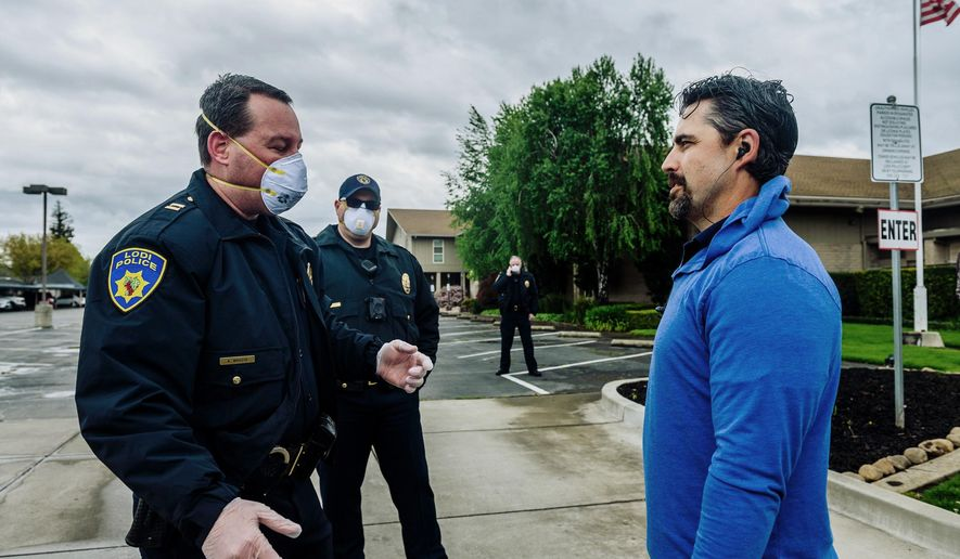 In this April 5, 2020, photo, Lodi Police Capt. Sierra Brucia, left, meets with Pastor Jon Duncan of the Cross Culture Christian Center on Palm Sunday in Lodi, Calif. The church sued Gov. Gavin Newsom arguing his stay-at-home order violated their constitutional rights. In San Joaquin County, part of California's vast Central Valley that produces most of the country's fruits and vegetables, the coronavirus is the leading cause of death this year and things will only worsen as infections skyrocket and hospitals fill beyond capacity. Like most of California, the city of Lodi is under a broad shutdown order as Christmas approaches, and its residents and businesses are grappling with how to stay safe while keeping their economy operating. (Daniel Kim/The Sacramento Bee via AP) **FILE**
