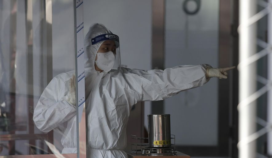 A medical worker wearing protective gear gestures at a coronavirus testing center in Seoul, South Korea, Saturday, Dec. 12, 2020. (AP Photo/Lee Jin-man)