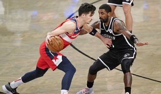 Brooklyn Nets guard Kyrie Irving (11) defends Washington Wizards forward Deni Avdija (9) as Avdija drives toward the Wizards basket during the second quarter of a preseason NBA basketball game, Sunday, Dec. 13, 2020, in New York. (AP Photo/Kathy Willens)  **FILE**
