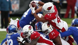Arizona Cardinals' Kenyan Drake (41), top right, leaps over New York Giants defenders to score a touchdown during the second half of an NFL football game, Sunday, Dec. 13, 2020, in East Rutherford, N.J. (AP Photo/Noah K. Murray)