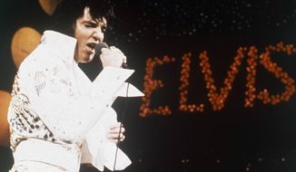 """FILE - This 1972 file photo shows Elvis Presley, the King of Rock """"n"""" Roll, during a performance. At one of three concerts at the Monroe Civic Center in 1974, Elvis Presley gave one of his necklaces to a local 5-year-old. A documentary from Elvis historian and fan Bud Glass traces how the King of Rock 'N Roll traces the history of the piece. (AP Photo/File)"""