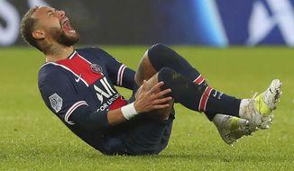 PSG's Neymar falls in pain during the League One soccer match between Paris Saint Germain and Lyon, at the Parc des Princes stadium in Paris, France, Sunday, Dec. 13, 2020. (AP Photo/Thibault Camus)