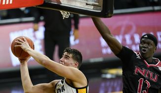 Iowa center Luka Garza drives to the basket past Northern Illinois center Adong Makuoi, right, during the first half of an NCAA college basketball game, Sunday, Dec. 13, 2020, in Iowa City, Iowa. (AP Photo/Charlie Neibergall)