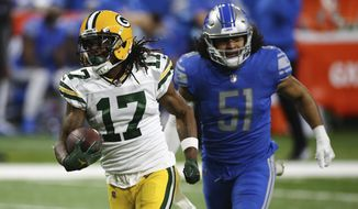 Green Bay Packers wide receiver Davante Adams (17) pulls away from Detroit Lions outside linebacker Jahlani Tavai (51) for a touchdown during the first half of an NFL football game, Sunday, Dec. 13, 2020, in Detroit. (AP Photo/Leon Halip)