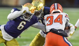 Syracuse running back Sean Tucker (34) is tackled by Notre Dame linebacker Jeremiah Owusu-Koramoah (6) during the third quarter of an NCAA college football game Saturday, Dec. 5, 2020, in South Bend, Ind. (Matt Cashore/Pool Photo via AP) **FILE**