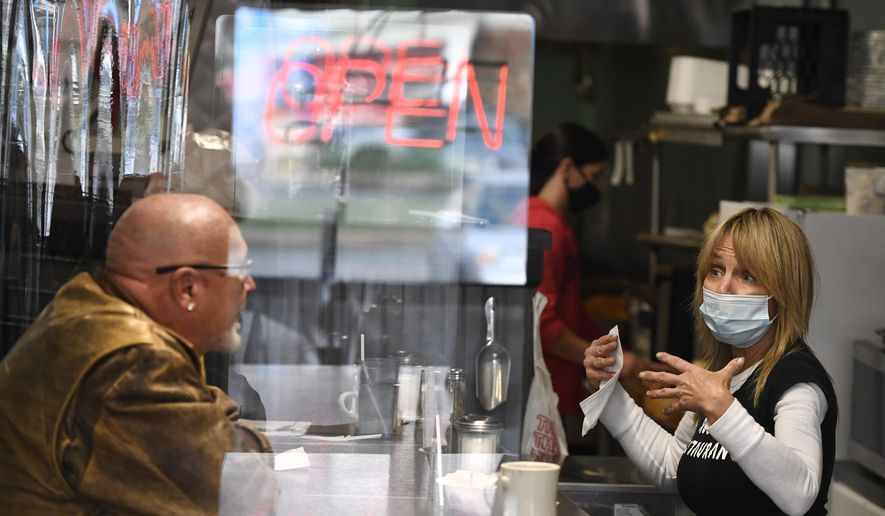 Head waitstaff Laurie Mitchell, right, talks with a customer at Rodd's Restaurant, Thursday, Dec. 10, 2020, in Bristol, Conn. Connecticut restaurant owners are concerned Gov. Ned Lamont will soon shut down indoor dining again and have taken steps to remain in business, like offering to go services, installing partitions and routinely cleaning and sanitizing areas. (AP Photo/Jessica Hill)