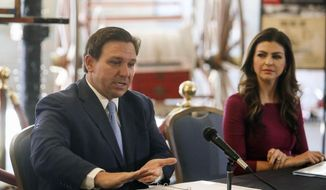Florida Gov. Ron DeSantis answers questions as his wife Casey DeSantis listens following a roundtable discussion regarding mental health at the Tampa Firefighter Museum, Friday, Dec. 11, 2020, in Tampa, Fla. (Ivy Ceballo/Tampa Bay Times via AP) ** FILE **