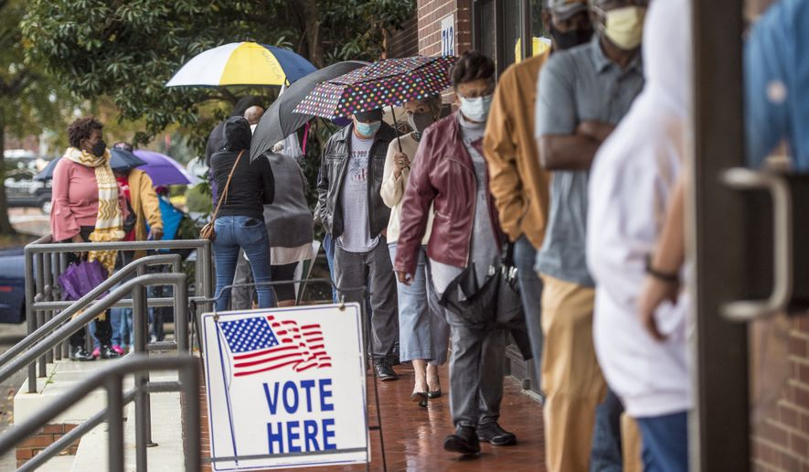 People wait in line on the first day of advance voting for Georgia's Senate runoff election at the Bell Auditorium in Augusta, Ga., Monday, Dec. 14, 2020. (Michael Holahan/The Augusta Chronicle via AP)