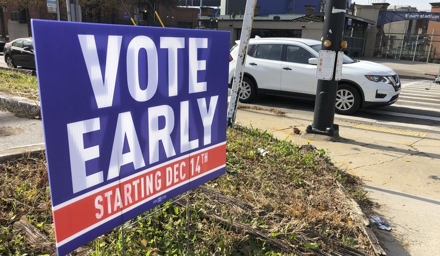 A sign in an Atlanta neighborhood on Friday, Dec. 11, 2020, urges people to vote early in Georgia's two U.S. Senate races. The early in-person voting period beginning Monday, Dec. 14, 2020, and lasting as late as Dec. 31 could determine the outcomes of races between Republican U.S. Sens. David Perdue and Kelly Loeffler and Democratic challengers Jon Ossoff and Raphael Warnock that will decide control of the U.S. Senate. (AP Photo/Jeff Amy)