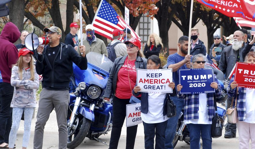 """Hundreds of supporters of President Donald Trump staged a defiant rally outside the New Mexico state Capitol building in Santa Fe, N.M., on Saturday, Nov. 7, 2020. They waved flags, chanted """"four more years,"""" and cheered and jeered at passing cars. A dozen supporters of Democrat Joe Biden gathered blocks away at the city's central plaza amid a heavy police presence. Democrat Joe Biden won the vote for New Mexico in the Nov. 3 election. (AP Photo/Morgan Lee) **FILE**"""