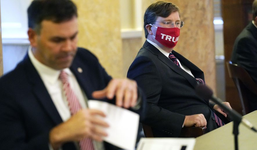 "Republican Gov. Tate Reeves, right, an ardent supporter of President Donald Trump, wears his ""Trump"" face mask as he waits while Secretary of State Michael Watson tends to the official duties overseeing the casting of votes in Mississippi's Electoral College, at the state Capitol in Jackson, Monday, Dec. 14, 2020. (AP Photo/Rogelio V. Solis)"