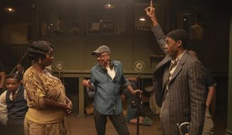 """This image released by Netflix shows Viola Davis as Ma Rainey, left, director George C. Wolfe, center, and Chadwick Boseman as Levee during the filming of """"Ma Rainey's Black Bottom."""" (David Lee/Netflix via AP)"""