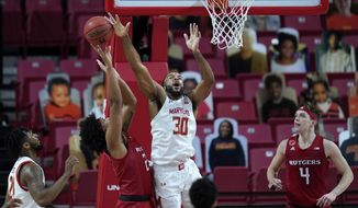 Maryland forward Galin Smith (30) blocks a shot by Rutgers guard Ron Harper Jr. during the first half of an NCAA college basketball game, Monday, Dec. 14, 2020, in College Park, Md. (AP Photo/Julio Cortez)