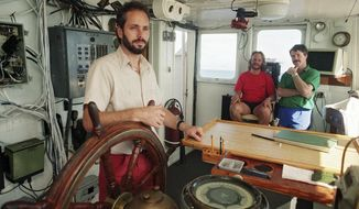 FILE - In this Aug. 29, 1991, file photo, Tommy Thompson, left, stands at the helm of the Arctic Explorer as Bob Evans, center, and Barry Schatz look on in Norfolk, Va. Thompson, a former deep-sea treasure hunter, is about to celebrate his fifth year in jail for refusing to disclose the whereabouts of 500 missing coins made from gold found in an historic ship wreck. Despite an investors lawsuit and a federal court order, Thompson still won't cooperate with authorities trying to find those coins, according to court records, federal prosecutors and the judge who found Thompson in contempt. (Doral Chenoweth III/The Columbus Dispatch via AP, File)