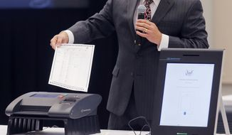 In this Thursday, Aug. 30, 2018, file photo, a Smartmatic representative demonstrates his company's system, which has scanners and touch screens with printout options, at a meeting of the Secure, Accessible & Fair Elections Commission in Grovetown, Ga. (Bob Andres/Atlanta Journal-Constitution via AP, File)