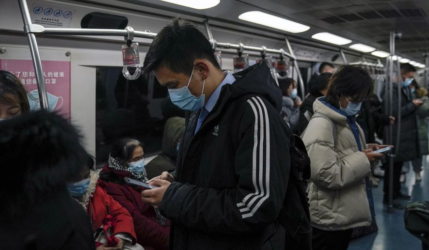 Commuters wearing face masks to help curb the spread of the coronavirus ride in a subway train in Beijing, Monday, Dec. 14, 2020. (AP Photo/Andy Wong)