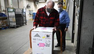 Minnesota Gov. Tim Walz lifts a just-delivered box of doses of the Pfizer-BioNTech COVID-19 vaccine, to get a sense of its weight, in the Minneapolis VA Hospital's loading dock Monday, Dec. 14, 2020. (Aaron Lavinsky/Star Tribune via AP, Pool)