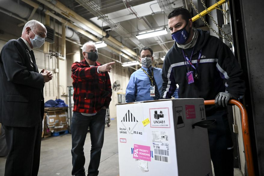 FedEx delivery driver Seth Warnecke delivers a box containing doses of the Pfizer-BioNTech COVID-19 vaccine to the Minneapolis VA Hospital Monday, Dec. 14, 2020. To his far left, is VA director Patrick Kelly and Minnesota Gov. Tim Walz. (Aaron Lavinsky/Star Tribune via AP, Pool)
