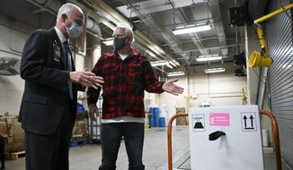 Minnesota Gov. Tim Walz speaks to Minneapolis VA Hospital Director Patrick Kelly after over doses of the Pfizer-BioNTech COVID-19 vaccine were delivered to the hospital Monday, Dec. 14, 2020. (Aaron Lavinsky/Star Tribune via AP,  Pool) **FILE**