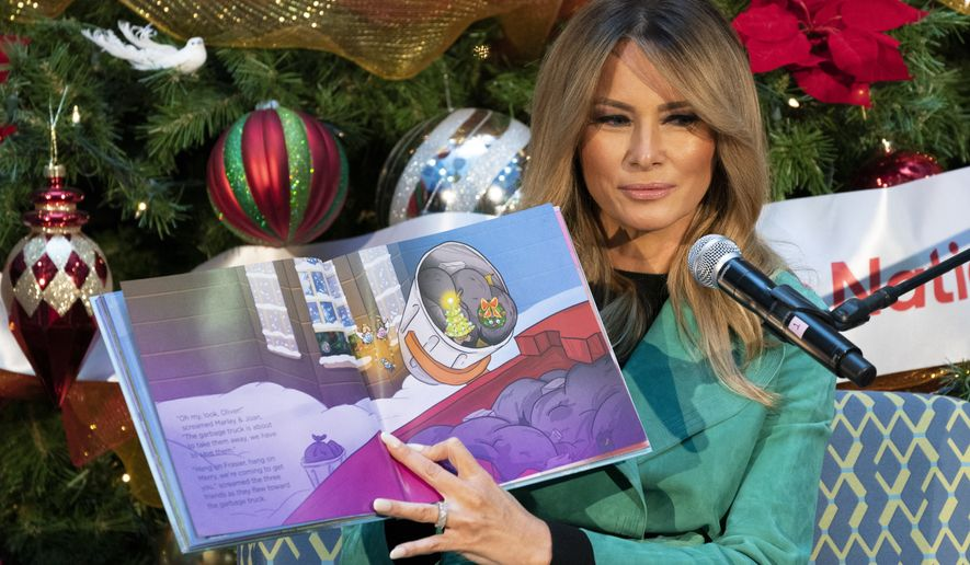 """First lady Melania Trump reads a Christmas book titled, """"Oliver the Ornament Meets Marley and Joan and Abbey,"""" at Children's National Hospital, Tuesday, Dec. 15, 2020, in Washington. Due to pandemic concerns there were two children in the room and the reading was broadcast to children in the rest of the hospital. (AP Photo/Jacquelyn Martin)"""