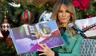 "First lady Melania Trump reads a Christmas book titled, ""Oliver the Ornament Meets Marley and Joan and Abbey,"" at Children's National Hospital, Tuesday, Dec. 15, 2020, in Washington. Due to pandemic concerns there were two children in the room and the reading was broadcast to children in the rest of the hospital. (AP Photo/Jacquelyn Martin)"
