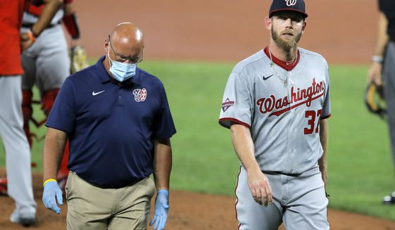 FILE - Washington Nationals starting pitcher Stephen Strasburg, right, walks with a member of the training staff as he heads to the dugout after leaving the game during the first inning of a baseball game against the Baltimore Orioles in Baltimore, in this Friday, Aug. 14, 2020, file photo. Washington Nationals general manager Mike Rizzo and manager Dave Martinez both expect Strasburg to be ready to go for spring training. (AP Photo/Julio Cortez, File)
