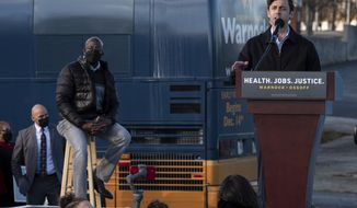 Democratic Georgia Senate challenger Jon Ossoff addresses supporters during a rally with the Rev. Rafael Warnock in Atlanta on the first day of early voting for the senate runoff Monday, Dec. 14, 2020. (AP Photo/Ben Gray)