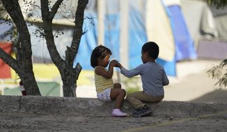 In this Tuesday, Nov. 18, 2020, file photo, children play at a camp of asylum seekers stuck at America's doorstep, in Matamoros, Mexico. Increasing numbers of parents and children are crossing the border, driven by violence and poverty in Central America and growing desperation in migrant camps in Mexico. U.S. Customs and Border Protection said Monday, Dec. 14, 2020 that it made 4,592 apprehensions of unaccompanied immigrant children in November, more than six times the figure in April. (AP Photo/Eric Gay File)