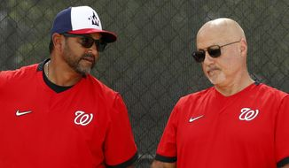 In this Feb. 17, 2020, file photo, Washington Nationals manager Dave Martinez, left, talks with general manager Mike Rizzo during spring training baseball practice in West Palm Beach, Fla. Nationals general manager Mike Rizzo says his top offseason priority is adding a middle-of-the-order hitter.  (AP Photo/Jeff Roberson, File). **FILE**