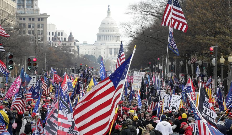 FILE - In this Saturday, Dec. 12, 2020, file photo, with the U.S. Capitol building in the background, supporters of President Donald Trump stand along Pennsylvania Avenue during a rally at Freedom Plaza, in Washington. Vandalism at four downtown Washington churches after rallies in support of Trump are exposing rifts among people of faith as the nation confronts bitter post-election political divisions. (AP Photo/Luis M. Alvarez, File)