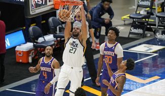 Utah Jazz center Rudy Gobert (27) dunks the ball as Phoenix Suns' Jevon Carter (4) and Damian Jones (30) look on during the second half of an NBA preseason basketball game, Monday, Dec. 14, 2020, in Salt Lake City. (AP Photo/Rick Bowmer)