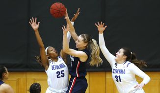 Connecticut guard Paige Bueckers (5) goes to the basket against Seton Hall guard Desiree Elmore (25) and forward Alexia Allesch (31) during the first half of an NCAA college basketball game, Tuesday, Dec. 15, 2020, in South Orange, N.J. (AP Photo/Noah K. Murray)