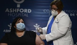 Yahaira Alicea, left, a respiratory therapist who treated the first two COVID-19 patients hospitalized in Puerto Rico, receives a vaccine in San Juan, Puerto Rico, Tuesday, Dec. 15, 2020.  Alicea has become the first person in the U.S. territory to be vaccinated against the virus. (AP Photo/Carlos Giusti)