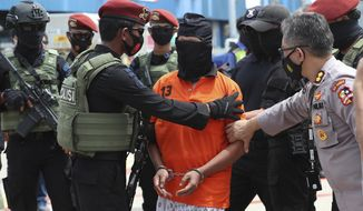 Police officers escort suspected militant Zulkarnaen, center, who is also known as Aris Sumarsono, upon arrival at Soekarno-Hatta International Airport in Tangerang, Indonesia, Wednesday, Dec. 16, 2020. Indonesian authorities have transferred suspected militants arrested in recent weeks to the country's capital, including Zulkarnaen, a bomb maker and the architect of a series of deadly attacks and sectarian conflicts in the world's largest Muslim majority nation. (AP Photo/Achmad Ibrahim)