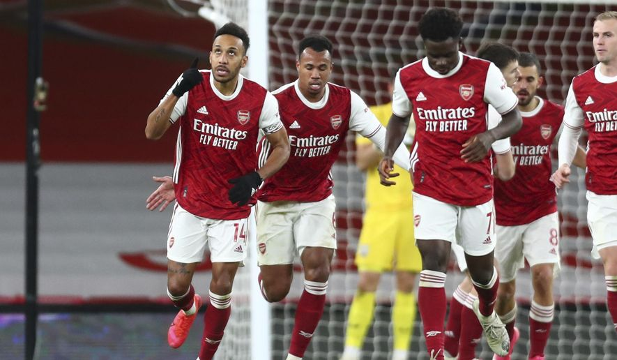 Arsenal's Pierre-Emerick Aubameyang, left, celebrates after scoring his side's first goal during an English Premier League soccer match between Arsenal and Southampton at the Emirates stadium in London, England, Wednesday, Dec. 16, 2020. (Clive Rose/Pool via AP)