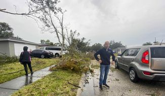 Debris is seen on the ground as residents survey damage along Elmhurst Drive after a possible tornado touched down in the area during a storm Wednesday, Dec. 16, 2020, in Pinellas Park, Fla. (James Borchuck/Tampa Bay Times via AP)