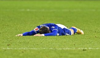 Schalke's Benito Raman lies on the ground during the German Bundesliga soccer match between FC Schalke 04 and SC Freiburg at the Arena in Gelsenkirchen, Germany, Wednesday, Dec. 16, 2020. (AP Photo/Martin Meissner, Pool)