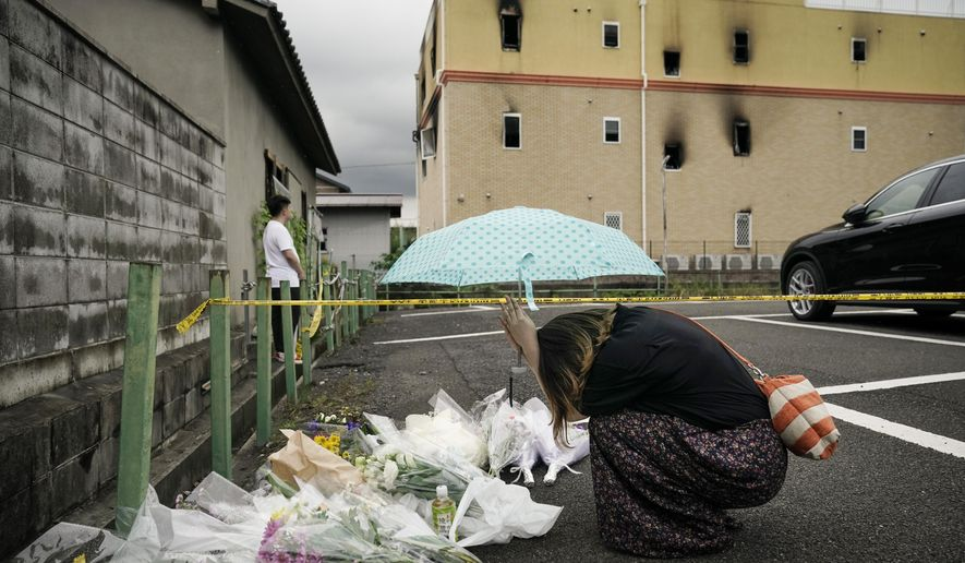 FILE - In this July 19, 2019, file photo, a woman prays at a makeshift memorial to honor the victims of a fire at the building of Kyoto Animation's No. 1 studio, background, in Kyoto, western Japan. Japanese prosecutors formally filed murder charges Wednesday, Dec. 16, 2020, against a suspect in the deadly fire at the Kyoto anime studio in 2019, after it was determined that he has recovered enough from his own severe burns and is mentally fit to stand trial. (AP Photo/Jae C. Hong, File)