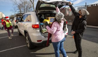 Volunteers load food into vehicles at the Meadowlands YMCA in East Rutherford, N.J., Tuesday, Dec. 15, 2020. The organization says it is giving away 200,000 meals per month to people with food insecurity at this location, more than doubled since the summer. (AP Photo/Ted Shaffrey)