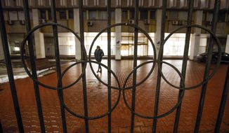 A man walks past a fence with Olympic Rings near the Russian National Olympic Committee building in Moscow, Russia, Thursday, Dec. 17, 2020. The Court of Arbitration for Sport confirmed Russia's flag and anthem are barred from next year's Olympics in Tokyo and the 2022 Winter Games in Beijing on Thursday. (AP Photo/Alexander Zemlianichenko)