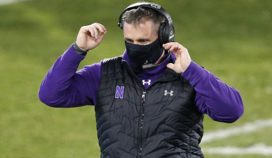 """FILE - Northwestern coach Pat Fitzgerald walks on the field during the fourth quarter of the team's NCAA college football game against Michigan State in East Lansing, Mich., in this Saturday, Nov. 28, 2020, file photo. Pat Fitzgerald figures he'll add a few more gray hairs by the time No. 15 Northwestern steps on the field to face No. 3 Ohio State in the Big Ten championship game on Saturday, Dec. 19. Then again, if Northwestern wins? """"Not gonna lie to you, it would be a helluva ride home on I-65,"""" Fitzgerald said.  (AP Photo/Al Goldis, File)"""