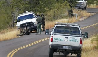 A pair of Customs and Border Patrol agents detain three migrants leading up to Montezuma's Pass in Coronado National Memorial, Thursday, Dec. 10, 2020, in Hereford, Ariz.   Construction of the border wall, mostly in government owned wildlife refuges and Indigenous territory, has led to environmental damage and the scarring of unique desert and mountain landscapes that conservationists fear could be irreversible. (AP Photo/Matt York)