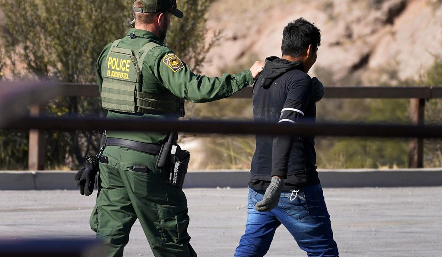 A Customs and Border Patrol agent detains a migrant atop Montezuma's Pass in Coronado National Memorial, Wednesday, Dec. 9, 2020, in Hereford, Ariz.  Construction of the border wall, mostly in government owned wildlife refuges and Indigenous territory, has led to environmental damage and the scarring of unique desert and mountain landscapes that conservationists fear could be irreversible. (AP Photo/Matt York)
