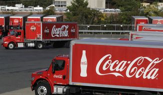 In this Oct. 14, 2019 photo a truck with the Coca-Cola logo, behind left, maneuvers in a parking lot at a bottling plant in Needham, Mass. The Coca-Cola Co. said Thursday, Dec. 17, 2020, it's laying off 2,200 workers, or 17% of its global workforce, as part of a larger restructuring aimed at paring down its business units and brands. (AP Photo/Steven Senne, File)  **FILE**