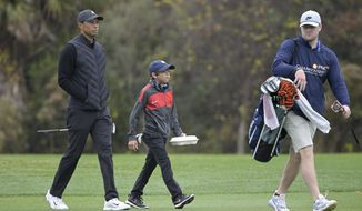 Tiger Woods, left, walks on the 11th fairway with his son Charlie during a practice round at the Father Son Challenge golf tournament, Thursday, Dec. 17, 2020, in Orlando, Fla. (AP Photo/Phelan M. Ebenhack)