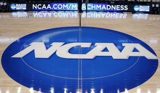 In this March 18, 2015, file photo, the NCAA logo is displayed at center court as work continues at The Consol Energy Center in Pittsburgh, for the NCAA college basketball tournament. (AP Photo/Keith Srakocic, File) **FILE**