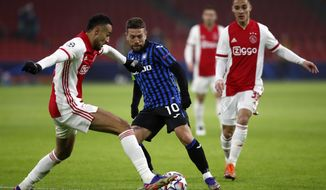 Ajax's Noussair Mazraoui, left, duels for the ball with Atalanta's Papu Gomez, centre, during the group D Champions League soccer match between Ajax and Atalanta at the Johan Cruyff ArenA in Amsterdam, Netherlands, Wednesday, Dec. 9, 2020. (AP Photo/Peter Dejong)