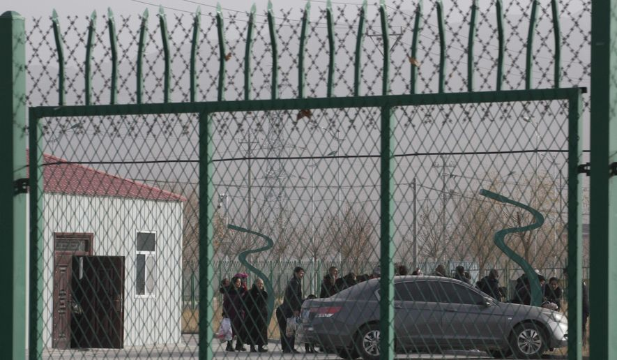 In this Dec. 3, 2018, file photo, people line up at the Artux City Vocational Skills Education Training Service Center at the Kunshan Industrial Park in Artux in western China's Xinjiang region. Groups representing ethnic minorities in China are again accusing the International Olympic Committee of ignoring widespread human rights abuses as the country prepares to hold the 2022 Winter Olympics in Beijing. Rights groups representing Tibetans, Uighurs, and others have sent an open letter to IOC President Thomas Bach and IOC member Juan Antonio Samaranch, who oversees preparations for the Beijing Games.(AP Photo/Ng Han Guan, File)