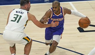 Phoenix Suns Chris Paul, right, drives as Utah Jazz forward Georges Niang, left,  defends during the first half of an NBA preseason basketball game Monday, Dec. 14, 2020, in Salt Lake City. (AP Photo/Rick Bowmer)